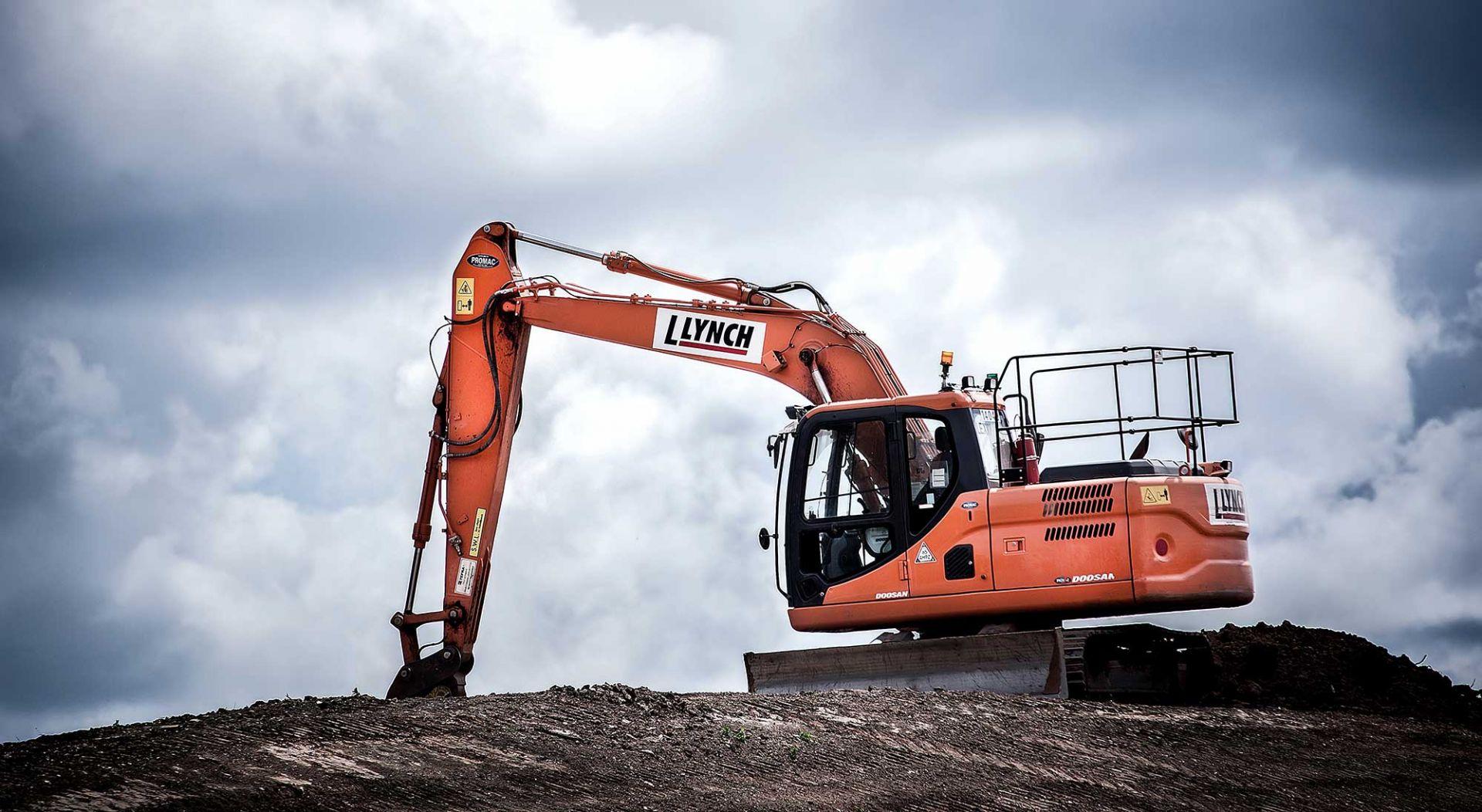 Large orange escavator working on mud hill.