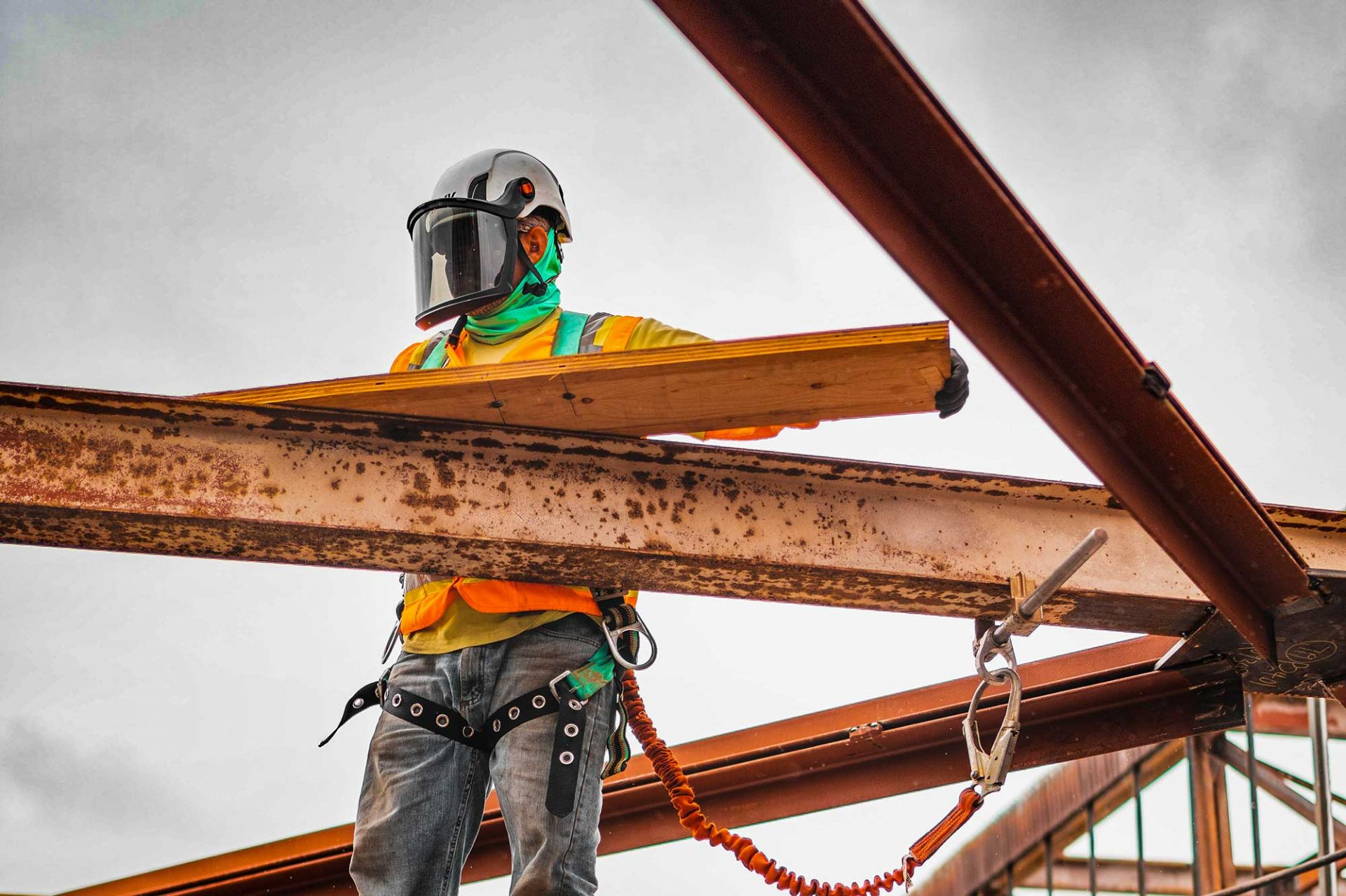 Close up of construction worker with large metal structure.